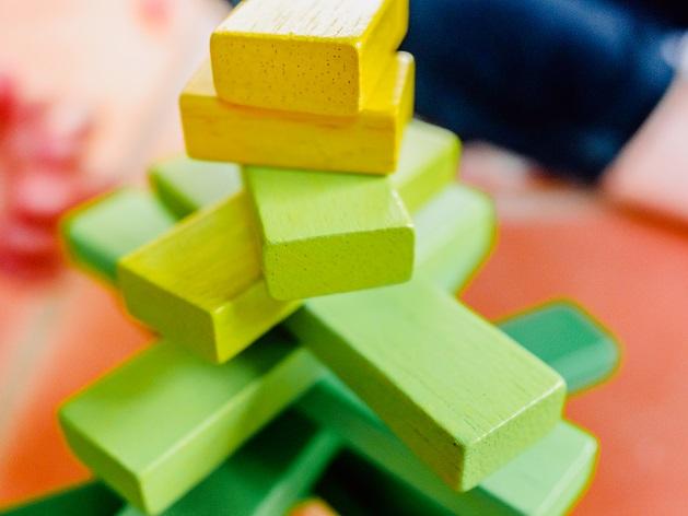 Des blocs de bois jaunes en équilibre dans une tour de jeu