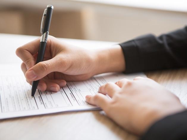 mains de femme remplissant un formulaire avec un stylo