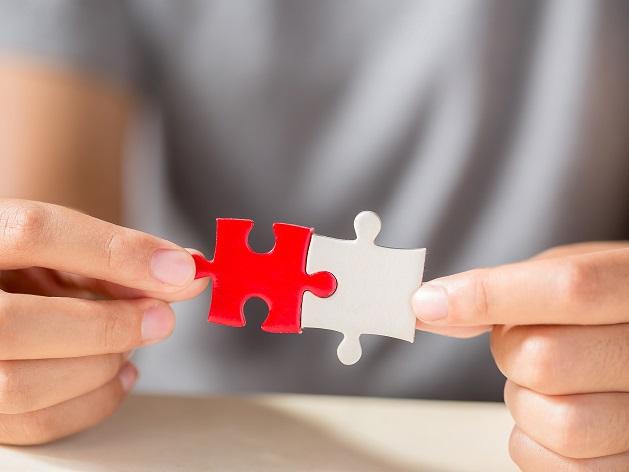 Mains tenant un morceau de puzzle